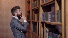 Un hombre en un traje se coloca delante del estante para libros en la biblioteca y elige un libro concepto de la biblioteca almacen de video