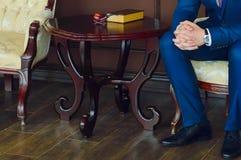 Un hombre en un traje se está sentando al lado de la tabla, sus manos es primer En la tabla es un libro y un tubo que fuma Interi imágenes de archivo libres de regalías