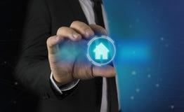 A un hombre en un traje y un lazo aparece en sus manos un gráfico futurista de la casa Concepto de: automatización casera, usos c Foto de archivo libre de regalías