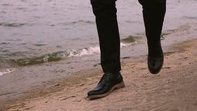 Un hombre en un traje y zapatos negros camina a lo largo del mar almacen de video