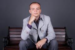 Un hombre en un capote gris se sienta en un marrón del banco de la calle Imagen de archivo
