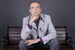 Un hombre en un capote gris se sienta en un marrón del banco de la calle Imágenes de archivo libres de regalías