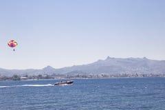 Un hombre en un paraplane está volando después de un barco ese las velas por el mar a Fotografía de archivo