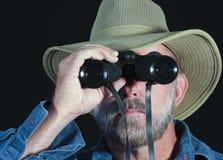 Un hombre en un sombrero del safari mira a través de los prismáticos Foto de archivo libre de regalías