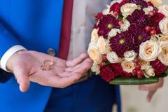 Un hombre en un traje azul está llevando a cabo los anillos de bodas en su palma fotos de archivo libres de regalías