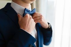 Un hombre en un traje costoso endereza su lazo Imágenes de archivo libres de regalías