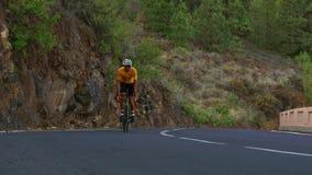 Un hombre en una bici del camino de los deportes monta en el alto localizado camino en las montañas metrajes