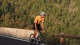 Un hombre en una bici del camino de los deportes monta en el alto localizado camino en las montañas almacen de metraje de vídeo
