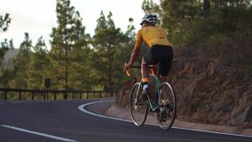 Un hombre en una bici del camino de los deportes monta en el alto localizado camino en las montañas almacen de video