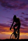 Un hombre en una bici que monta la silueta delantera en la puesta del sol Foto de archivo