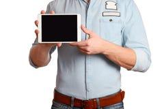 Un hombre en una camisa azul clara y vaqueros con una correa marrón está sosteniendo la PC de la tableta aislada en el fondo blan imagen de archivo