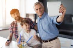 Un hombre en una camisa azul hace el selfie en la cocina con su nieto e hijo Están sonriendo Foto de archivo libre de regalías