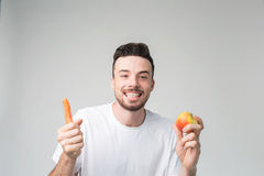 Un hombre en una camisa blanca aislada en un fondo ligero que sostiene la zanahoria y la manzana Imagen de archivo libre de regalías