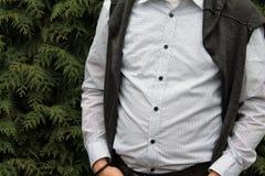 Un hombre en una camisa blanca del lunar contra un fondo del tuja Imagenes de archivo