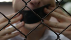Un hombre en una camisa blanca está detrás de una red y cubre su boca con la cinta escocesa, no-acceso de la información, liberta almacen de metraje de vídeo