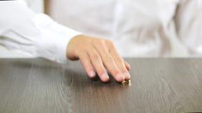 Un hombre en una camisa blanca saca un anillo de compromiso de su finger Decisión sobre divorcio almacen de metraje de vídeo