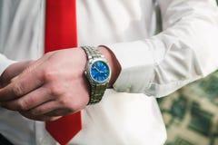Un hombre en una camisa blanca y un lazo rojo pone un reloj en su brazo fotos de archivo