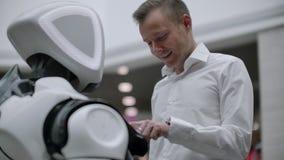Un hombre en una camisa comunica con un robot blanco que hace preguntas y que presiona la pantalla con sus fingeres metrajes
