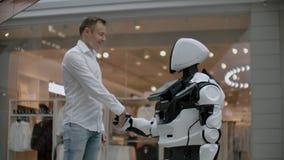 Un hombre en una camisa comunica con un robot blanco que hace preguntas y que presiona la pantalla con sus fingeres almacen de video