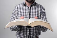 Un hombre en una camisa a cuadros que sostiene un libro negro en un fondo ligero Estudiante barbudo Fotos de archivo