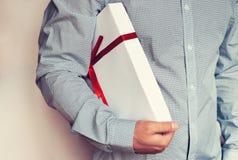 Un hombre en una camisa de la luz sostiene una caja de regalo blanca con una cinta roja en su mano tono Imagenes de archivo