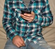 Un hombre en una camisa en el sofá con el teléfono móvil a disposición imagen de archivo libre de regalías