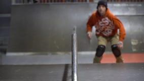 Un hombre en una camiseta de la naranja patina en un parque en los rodillos, cámara lenta del patín metrajes