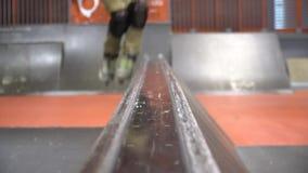 Un hombre en una camiseta de la naranja patina en pcteres de ruedas en un parque del patín, cámara lenta Niffty almacen de video