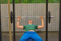 Un hombre en una camiseta verde y pantalones azules que hacen una prensa de banco de la barra, imagen de archivo libre de regalías