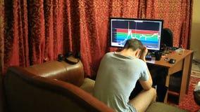 Un hombre en una camiseta y los pantalones cortos, sentándose en casa en el sofá, los monitores cambia en el horario en el interc almacen de metraje de vídeo