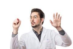 Un hombre en una capa blanca con un marcador rojo sobre un vidrio transparente Fotos de archivo