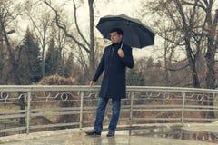 Un hombre en una capa camina en el parque de la primavera imagen de archivo libre de regalías