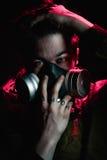 Un hombre en una careta antigás en un fondo negro Imagen de archivo