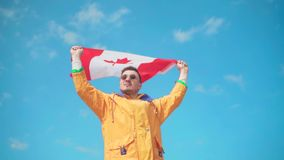 Un hombre en una chaqueta amarilla, tejanos y vidrios se coloca en las montañas y sostiene la bandera canadiense con ambas manos metrajes
