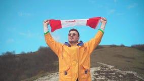 Un hombre en una chaqueta amarilla, tejanos y vidrios se coloca en las monta?as y sostiene la bandera canadiense con ambas manos almacen de metraje de vídeo