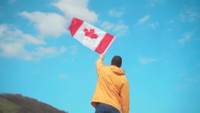 Un hombre en una chaqueta amarilla, tejanos y vidrios se está colocando en las montañas y está agitando la bandera canadiense almacen de metraje de vídeo