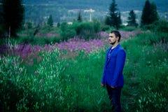 Un hombre en una chaqueta azul en un prado de la flor imagen de archivo libre de regalías