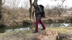 Un hombre en una chaqueta con una capilla encendido está caminando en un parque de la primavera almacen de metraje de vídeo