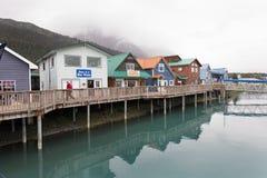Un hombre en una chaqueta roja camina a lo largo del paseo marítimo en el puerto del bote pequeño con los edificios históricos co fotografía de archivo libre de regalías