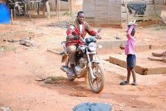 Un hombre en una motocicleta en un pueblo Fotografía de archivo libre de regalías