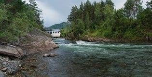 Un hombre en una pasarela de la suspensión entre los bancos rocosos de un río de la montaña y central hidroeléctrica abandonada e foto de archivo libre de regalías