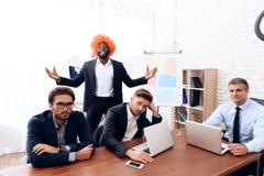 Un hombre en una peluca vino a una reunión de negocios Imagenes de archivo