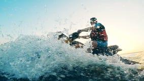 Un hombre en una vespa del agua está salpicando la cámara con agua mientras que conduce metrajes