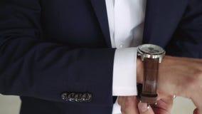 Un hombre en un vestido del traje de negocios mira a mano Manos de reloj del botón del hombre de negocios en el primer metrajes