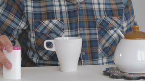 Un hombre en vez del azúcar añade el edulcorante al café metrajes