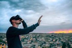 Un hombre en vidrios de la realidad virtual en el fondo de una puesta del sol sobre la ciudad Concepto de tecnologías futuras mod imágenes de archivo libres de regalías