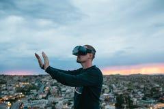 Un hombre en vidrios de la realidad virtual en el fondo de una puesta del sol sobre la ciudad Concepto de tecnologías futuras mod imagen de archivo libre de regalías