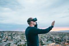 Un hombre en vidrios de la realidad virtual en el fondo de una puesta del sol sobre la ciudad Concepto de tecnologías futuras mod imagenes de archivo