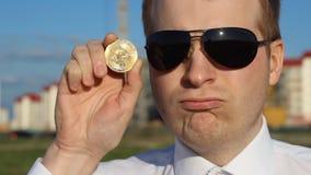 Un hombre en vidrios negros está llevando a cabo un bitcoin en su mano y es plan triste, triste, rizado almacen de metraje de vídeo