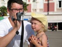 Un hombre en vidrios y una niña en un sombrero amarillo están grabando D?a de verano caliente soleado imagen de archivo